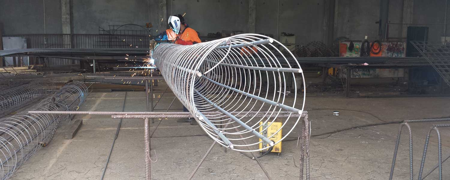 man welding reinforcing to make a pile cage.